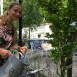 georgina verbaan watert met liefde haar gouden iep bij pipowagen deluxe buitengoed de gaard