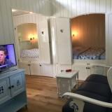 ruime woonkamer met bankstel en smart tv in pipowagen deluxe heythuysen buitengoed de gaard